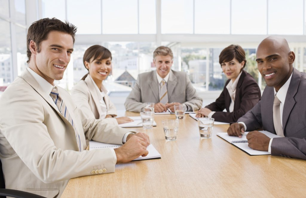 Portrait of happy business colleagues sitting together at meeting in boardroom