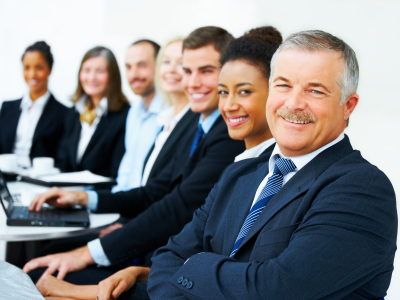 Cheerful senior business man in an office environment with his colleagues in the background